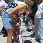 Coach Annie Cheeney adjusting a young cyclists saddle